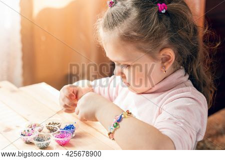 A Little Girl Is Engaged In Needlework, Making Jewelry With Her Own Hands, Stringing Multi-colored B