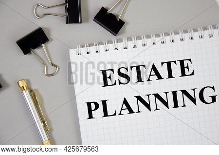 Estate Planning - Business Concept Word Written On Gray Background With Pencils And Paper Clips