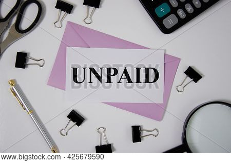 Unpaid Word Written On Pink Envelope Near Office Supplies