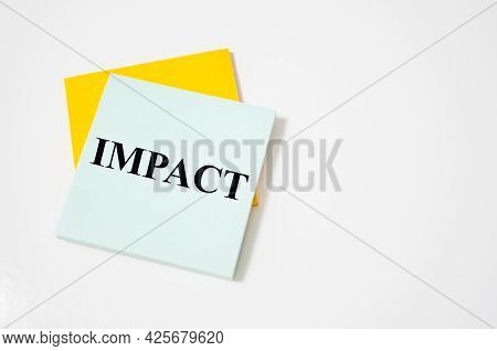Impact Text Written On A White Notepad With Colored Pencils And A Yellow Background