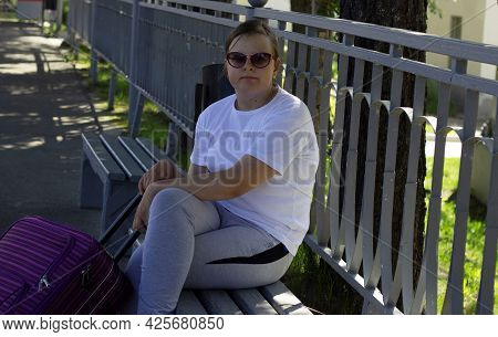 A Beautiful Girl, Wearing Dark Glasses, In Light Clothes, Is Sitting On A Peron, On A Bench, Holding