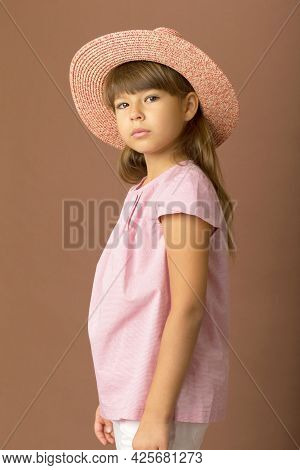 Girl In Stylish Summer Clothes And Straw Hat. Girl With Ponytails Wearing Pink Blouse, White Pants A