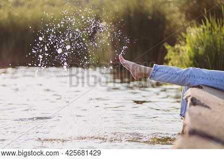 Girl In Light Blue Jeans Play With Water On The Lake In Sunlight.  Summer Background.