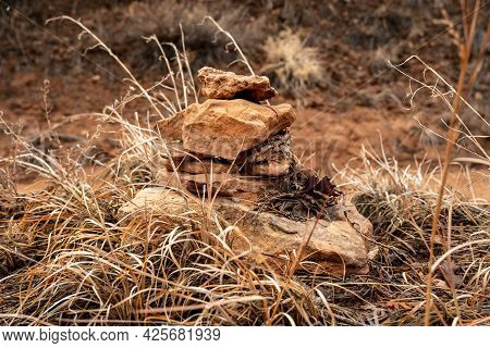 Rock Cairn Sits On A Grassy High Point In The Dry Wash Of A Hiking Trai In Canyonlands