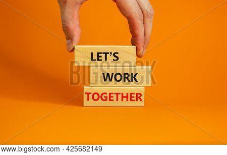 Work Together Symbol. Wooden Blocks With Words Let Is Work Together On Beautiful Orange Background.
