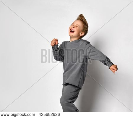 Little Boy Child With European Appearance Studio Shot In Motion. Preteen Blond Male Child Wearing Tr