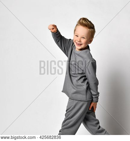 Little Boy With Happy Smile Turning Back And Pointing Finger To Camera Studio Shot Against White Bac