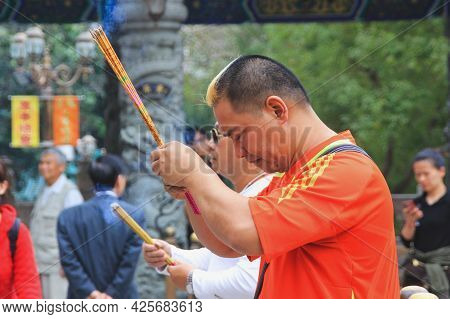 Asian Attractive Stylish Young Man Wearing Casual Pray Selflessly With Holding Burned Incense Sticks
