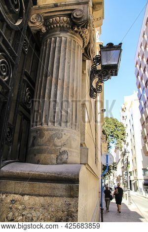 Alicante, Spain- June 26, 2021:old Facade With Stone Pillars And Vintage Streetlight In A Majestic B
