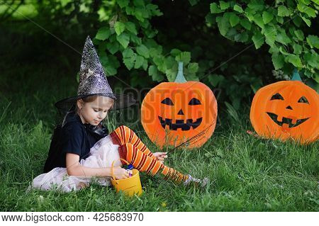 Happy Halloween Day. Little Girl Dressed In A Witch Costume Holds A Bucket Of Sweets And Candy In Au
