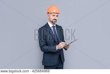 Confident Businessman In Helmet Hold Folder. Safety Business Expertise. Man In Hardhat Making Notes.