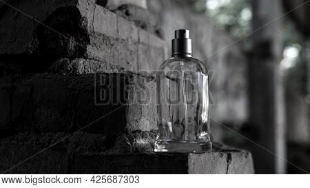 Men's Perfume With Copy Space. A Jar Of Perfume On The Background Of A Brick Wall.
