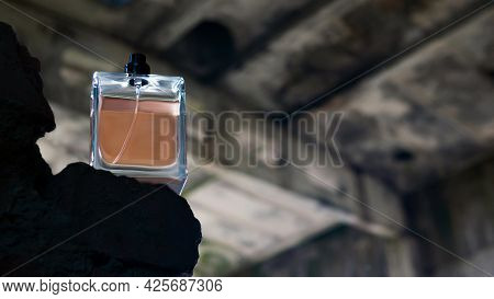 A Bottle Of Men's Perfume On The Background Of Architectural Ruins. Orange Perfume.