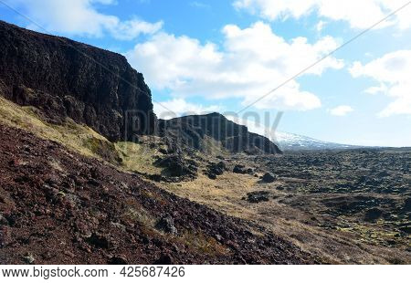 Lava Rock Landscape With Snow Covered Mountains In The Distance.