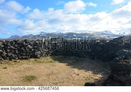 Scenic Lava Rock Animal Pen With Snow Covered Mountains In The Summer.
