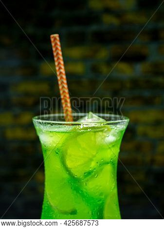Green Lemonade On The Bar, Green Alcoholic Cocktail, Close-up Drink With Ice.