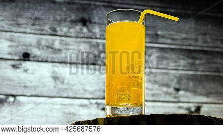 Yellow Lemonade In A Glass Transparent On A Background Of Wooden Boards. Orange Juice.