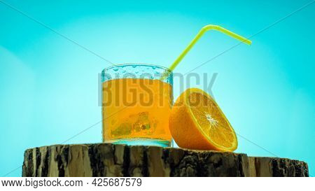 Yellow Lemonade In A Transparent Glass On A Blue Background. Orange Juice.