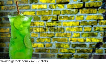 Cocktail In A Glass On A Brick Wall Background. Green Lemonade With Ice. Summer Fresh Drink In A Tal