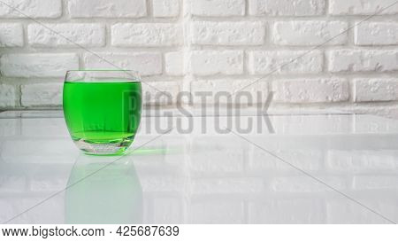Green Lemonade On A White Brick Wall Background. Green Drinking Drink In A Glass