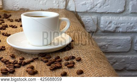 Coffee In A Cup On A White Brick Wall Background. A Cup Of Coffee On A Bar Counter With A Sprinkle O
