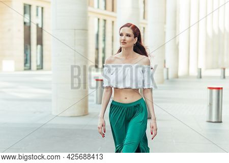 Beautiful Red-haired Woman In Her Thirties In A Blouse And Green Skirt Walks In The Summer.