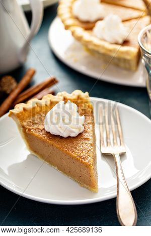 Traditional Pumpkin Pie With Whipped Cream And Cinnamon