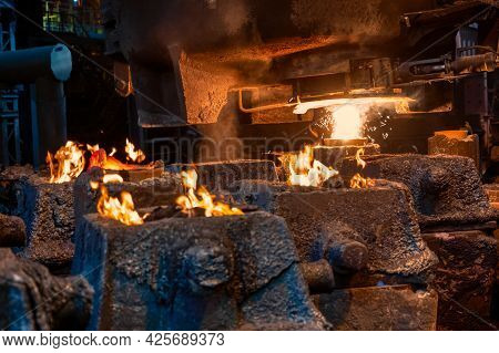 Steel Molds For Metal Pouring. A Fire Burns At The Top Of The Molds.
