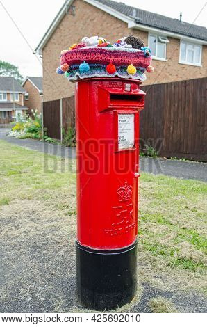 Basingstoke, Uk - July 3, 2021:  Traditional Royal Mail Red Pillar Box Topped By A Knitted And Croch