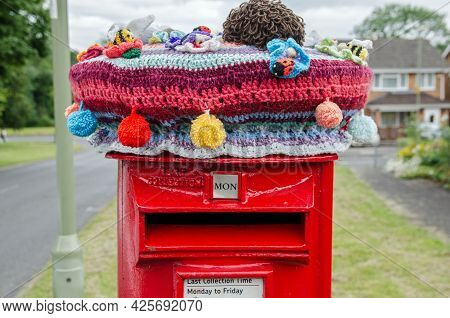Basingstoke, Uk - July 3, 2021: A Crochet And Knitted Woollen Decoration On Top Of A Traditional Red