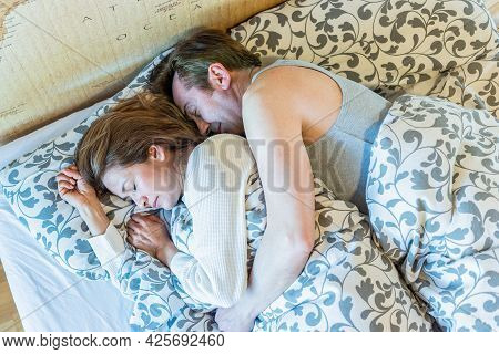 Mature Couple Sleeping In Bed. Top View.
