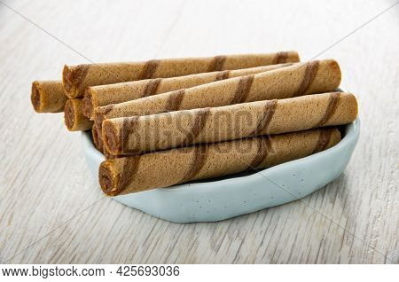 Brown Striped Wafer Rolls In Light-blue Small Bowl On Wooden Table