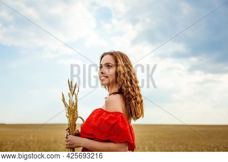Young Beautiful Woman In Golden Wheat Field. Happy Woman In Red Dress Enjoying Life In Field. Nature