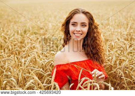 Style Redhead Young Woman In Red Clothe Tay View Yellow Wheat Nature. Cute Girl Smiles With A Snow-w