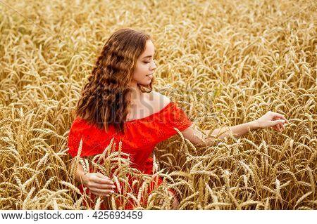 Style Redhead Girl In Red Dress Tay On Yellow Wheat Field Caucasian Real Girl. Happy Woman Enjoying