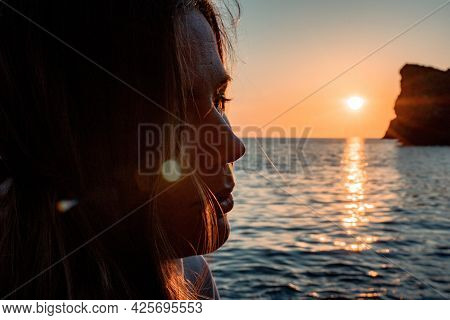 A Young Tourist Woman Holding Coffee Tumbler Cup While Sitting Outdoor And Enjoying Sunrise Over Sea