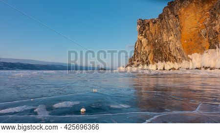 A Granite Rock, Devoid Of Vegetation, Rises Above The Frozen Lake. Steep Slopes, Icicles At The Base