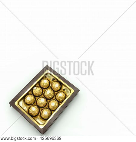 Brown Cardboard Box With Chocolates. The Candies Are Wrapped In Golden Foil. Top View. Isolated Over