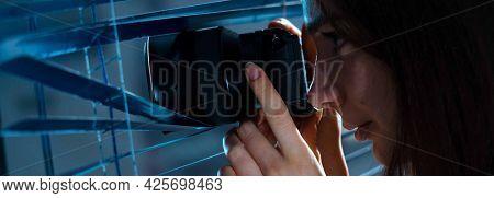 paparazzi girl secretly takes photos through the window. Young woman Paparazzi photographer take a photo suspiciously from around a jalousie while using a camera
