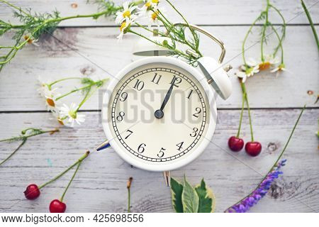 Summer Time Background. White Alarm Clock Arrows Noon On A Wooden Table Around Wildflowers Fresh Ber