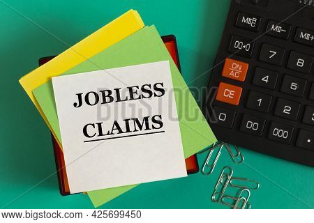 Jobless Claims - Words On Note Paper Against The Background Of A Calculator And Paper Clips. Busines