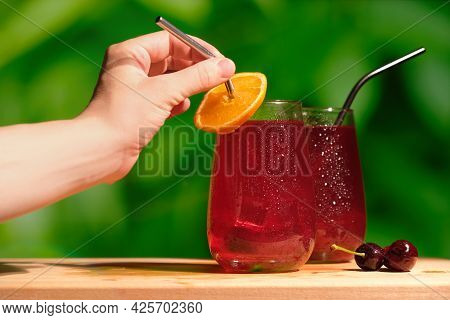 Summer Drinks Concept. Woman Drinking Summer Cherry Cocktail Made Of Gin And Cherry Juice Decorated