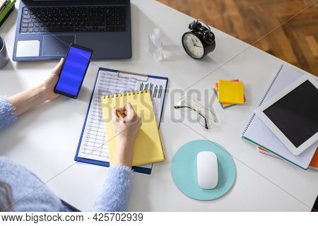 Young Freelancer Woman Using Smartphone While Working At Home Office. Female Freelancer Working From