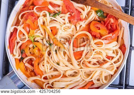 Vegetarian Linguini Pasta With Tomatoes And Bell Peppers In A Frying Pan, Top View, Close-up