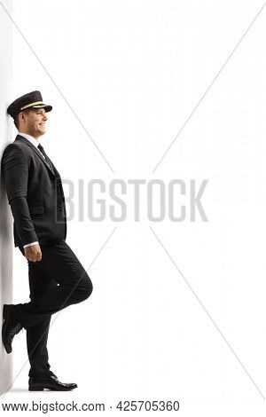 Full length profile shot of a chauffeur in a uniform leaning on a wall isolated on white background