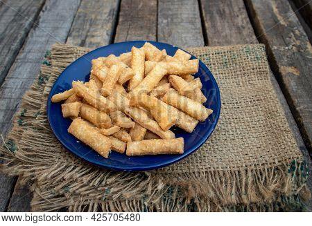 Closeup Of Salted Namak Para Or Nimki Indian Crunchy Savoury Snack In A Blue Plate With Burlap Fabri