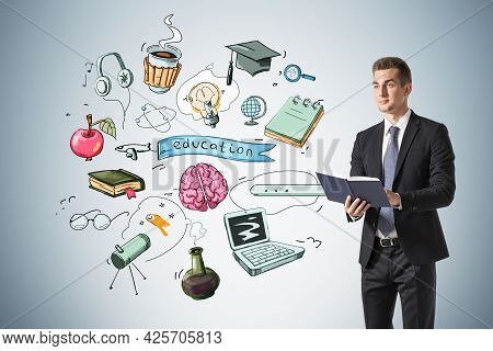 Businessman In Suit Is Holding A Book, Range Of Educational Icons Are Drawn Behind On Light Blue Wal