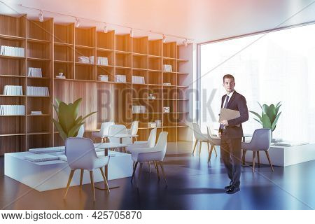 Thoughtful Handsome Businessman In Suit Holds Clipboard And Dreaming About Corporate Career. Corpora