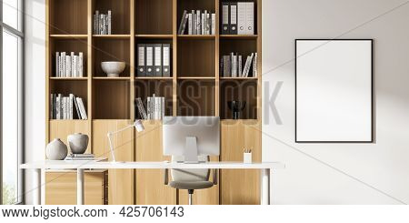 Empty White Poster On The Wall. Wooden Book Cabinet Behind Computer On White Desk With Wooden Drawer