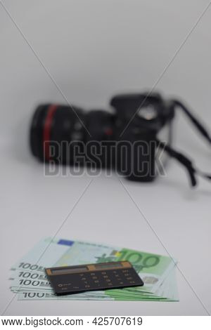 The Calculator Lies On One Hundred Euro Banknotes Against The Background Of A Camera, Earnings On Ph